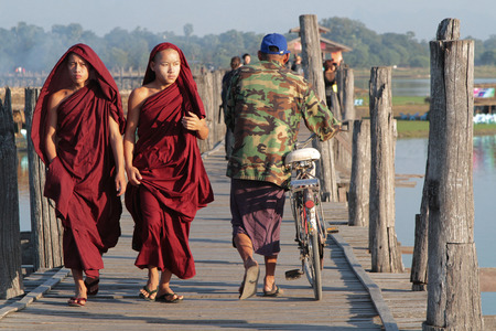 teakwood: MANDALAY, MYANMAR, December 11, 2014 : People walk on U-Bein bridge at sunset. The 1,5 kilometre bridge was built around 1850 and is believed to be the oldest and longest teakwood bridge in the world. Editorial