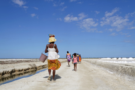 evaporation: BELO, MADAGASCAR, November 24, 2015 : Women walk on the road near salt evaporation ponds of Belo-sur-Mer, where families work to extract salts from sea water. Editorial