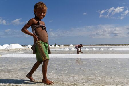 evaporacion: BELO-sur-Mer, Madagascar 24 de noviembre de 2015: Una ni�a sonriente camina descalzo cerca de la salina en los que trabaja su madre.