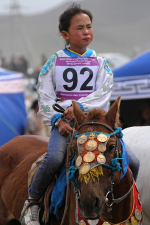 mongolia horse: KARKORIN, MONGOLIA, July 8, 2013 : Young girl rides during Naadam. Naadam is a traditional festival where Mongolian wrestling, horse racing, and archery are held throughout the country during midsummer