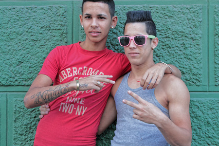 two people with others: CIENFUEGOS, CUBA, February 17, 2014 : Two boys in the street. While Cuba opens gradually, many young people prefer to leave the country, but others take advantage of it to develop their business. Editorial