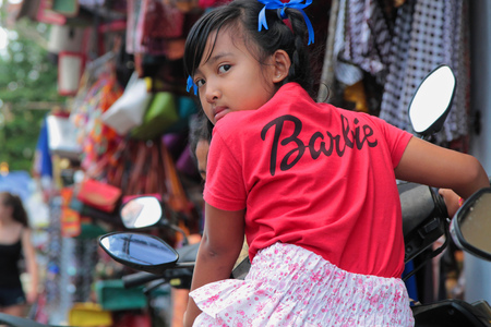 barbie: BALI, INDONESIA, August 12, 2014 : A barbie girl rides a motorbike in the market streets of Ubud.