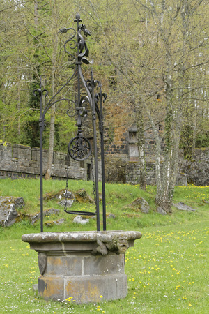 owes: PONTGIBAUD, FRANCE, May 6, 2016 : An old well in Chateau-Dauphin medieval castle. The castle owes its name to the coat of arms of the Count of Auvergne who built it in the 12th century.