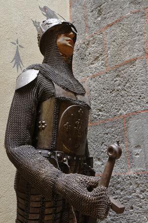 owes: PONTGIBAUD, FRANCE, May 6, 2016 : A knight in armour in Chateau-Dauphin medieval castle. The castle owes its name to the coat of arms of the Count of Auvergne who built it in the 12th century