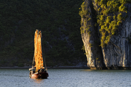 CAT BA, VIETNAM, October 27, 2016 : Traditional junk sails in the evening in Cat Ba Archipelago, the southeastern edge of Ha Long Bay. Ha Long Bay has been inscribed in the World Heritage List according to its limestone karstic geomorphologic features.