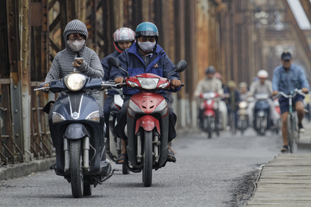 mopeds: HANOI, VIETNAM, Octobre 31, 2016 : Long Bien bridge is a historic cantilever bridge across the Red River in Hanoi, used by trains, mopeds, bicycles and pedestrians.