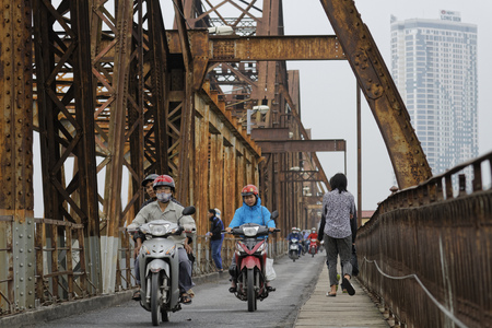 mopeds: HANOI, VIETNAM, October 31, 2016 : Long Bien bridge is a historic cantilever bridge across the Red River in Hanoi, used by trains, mopeds, bicycles and pedestrians.