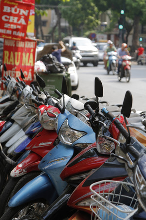 trafic: HANOI, VIETNAM, October 22, 2016 : Lots of motorbike parked along an avenue of Hanoi. Transportation of persons in Hanoi is mainly made by small motor bikes. Editorial