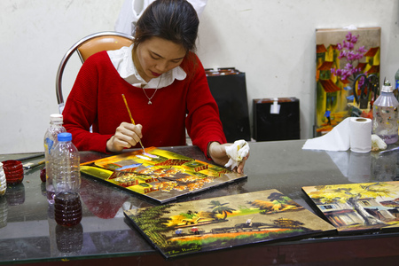 lacquerware: HANOI, VIETNAM, October 30, 2016 : Unidentified artist paints in a workshop of lacquer of Hanoi. Lacquerware are objects decoratively covered with lacquer, mostly from East Asian cultures.