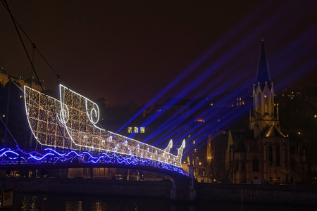 LYON, FRANCE, December 7, 2016: A light boat on the pedestrian bridge over Saone river. The Festival of Lights (French: Fete des lumières) express gratitude Toward Mother Mary December 8th around with different light shows Each year. Editorial