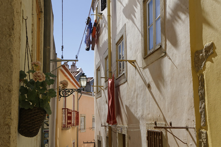 LISBON, Portugal, April 5, 2017 : A small street in Alfama. Alfama is the oldest district of Lisbon, spreading on the slopes between the Sao Jorge Castle and the Tagus river.