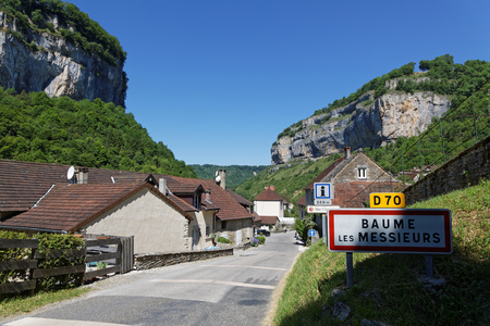 The village of Baume-les-Messieurs lies within the most extensive of the steephead valleys of the Jura escarpment, the Reculee de Baume, limestone cliffs about 200m high. Stock Photo