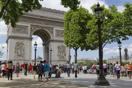 PARIS, France, June 15, 2017 : Tourists visit the Place Charles de Gaulle, historically known as the Place de lEtoile, and the Arc de Triomphe, which stands at the center of the Place.