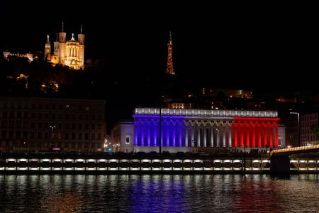 LYON, FRANCE, July 14, 2017 : The city of Lyon commemorates Bastille Day (French National Day) by a lightning of french colors on Palais de Justice, with Fourviere Basilica in the background. Editorial