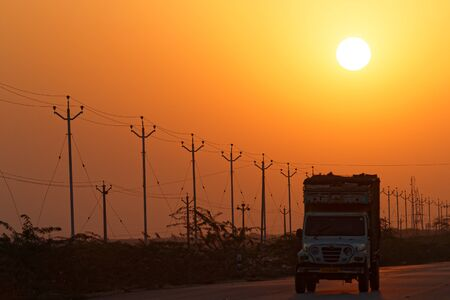 POKHARAN, INDIA, November 3, 2017: Sunrise on the highway and electric wires. Editorial