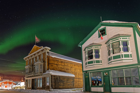 DAWSON CITY, YUKON, CANADA, March 12, 2019 : Northern Lights above the old houses of the Gold Rush City.
