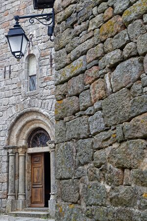 Old church entrance in the medieval village of La Garde Guerin, in Lozere, France
