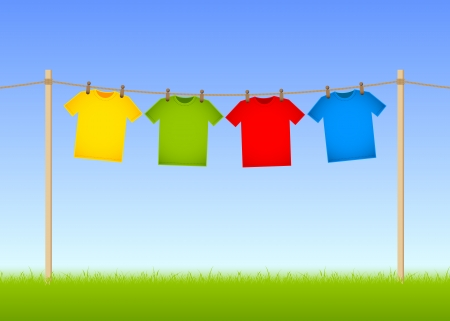 clothes peg: Hung T-shirts on washing line with grass and blue sky in the background