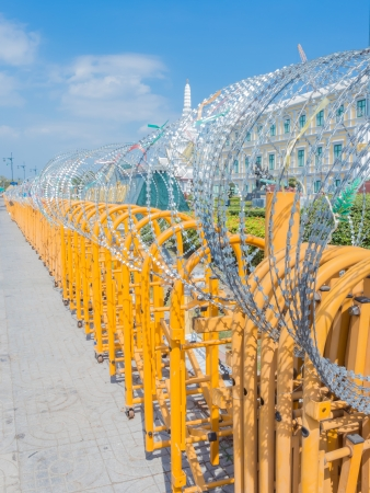 Barbed wire on yellow metal fence in Bangkok Thailand photo