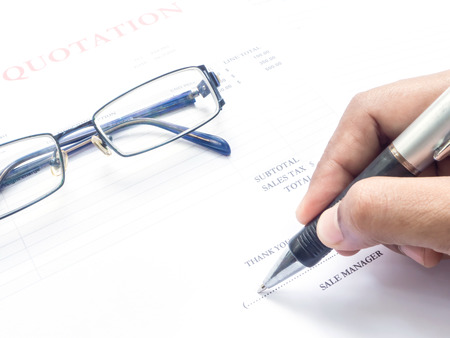 contractual: Close up showing fingers  holding a pen to sign on  document and glasses Stock Photo