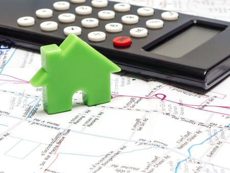 Green house and calculator on the map , property concept