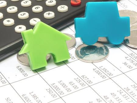 青い車と電卓とコイン財務会計伝票上の緑の家 写真素材