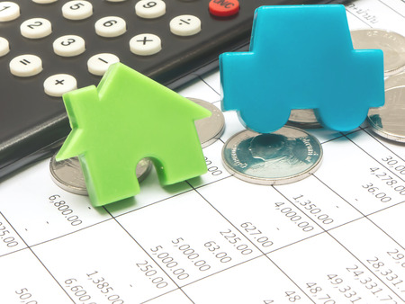 blue car and green house over financial accounting document with calculator and coin Foto de archivo