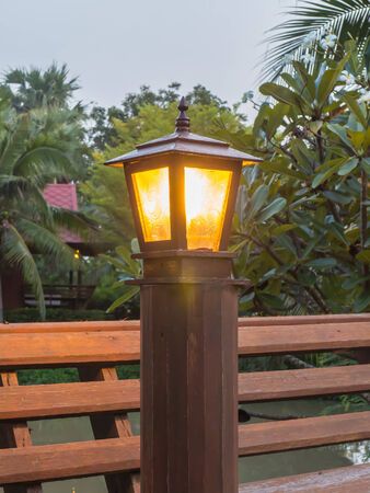 lit lamp: Lit lamp post at the garden in evening