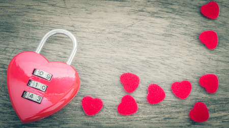 close uo: Close uo red key and pieces of fabric heart shape on old wooden desk.vintage filter effect