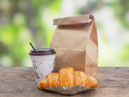Breakfast to go,coffee and croissant with paper bag on wooden table over green defocused background