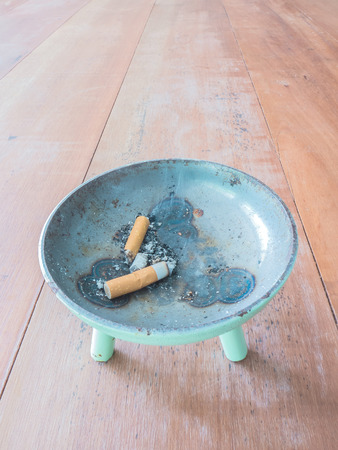 ashtray: cigarette and metal ashtray on  wooden table