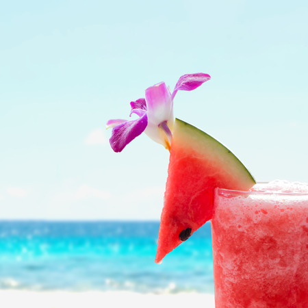 watermelon juice: Close up piece of watermelon on the top of watermelon juice glass over blurred summer beach background