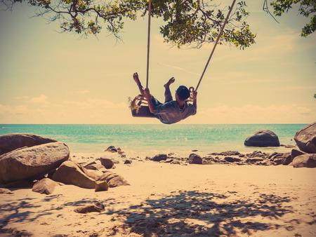 若い男が熱帯の夏のビーチ、ビンテージ フィルター効果でスイングでスイング 写真素材