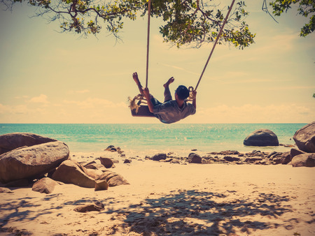 Young man swinging in a swing on tropical summer beach, vintage filter effect