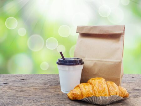 coffee and croissant with paper bag on wooden table over green defocused background