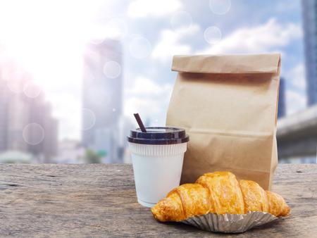 コーヒーとクロワッサン、都市の景観上の木製のテーブルに紙の袋の背景をぼかし 写真素材