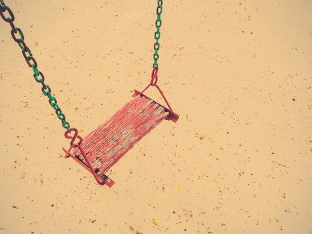 Empty old chain swings on over sand playground, vintage filter effect photo