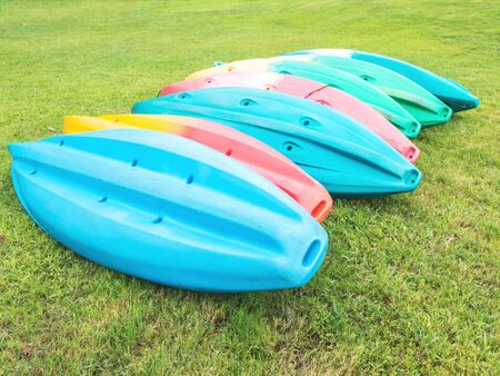 Colorful kayaks turn upside down on grass in the park