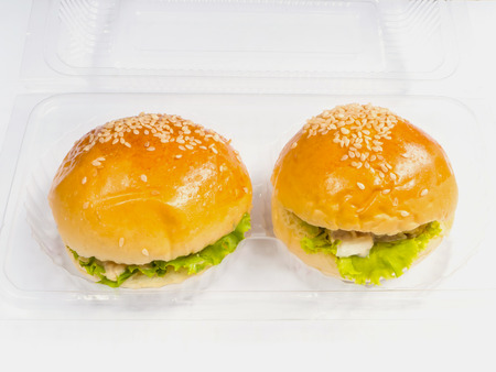 two piece: Close up plastic take away package with two piece of small hamburgers inside