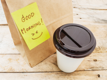 morning tea: Take away cup of coffee and paper bag with note Good morning Stock Photo