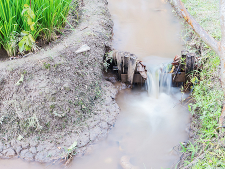 farm background: small water dam with soft focus near by rice field in Thailand Stock Photo