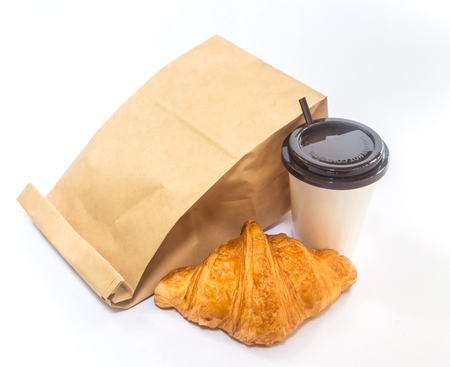 breakfast: Desayuno para llevar, café y croissant con bolsa de papel en el fondo blanco