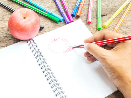 pen and paper: Hand holding pen to draw red apple on white notepad