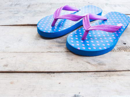 to flop: Blue flip flop with pink heart pattern on wood background
