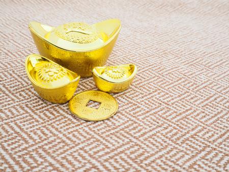 ingots: Chinese new year ornament, Gold ingots on beige tweed fabric background Stock Photo