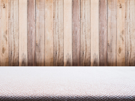 tweed: Beige tweed fabric tablecloth and wooden background for product display