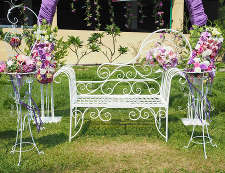 wedding backdrop: white bench and flowerpot stand with beautiful flower for wedding outdoor party