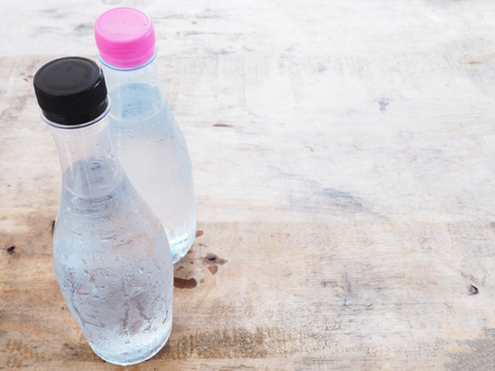 envases de plástico: agua fría botella de plástico sobre la mesa de madera