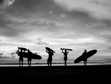 Silhouette Of surfer people carrying their surfboard on sunset beach, black and white color