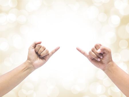 dedo meÑique: Dos manos que sostienen el dedo algo más de fondo de oro bokeh desenfoque. Promesa o signo concepto de usar.